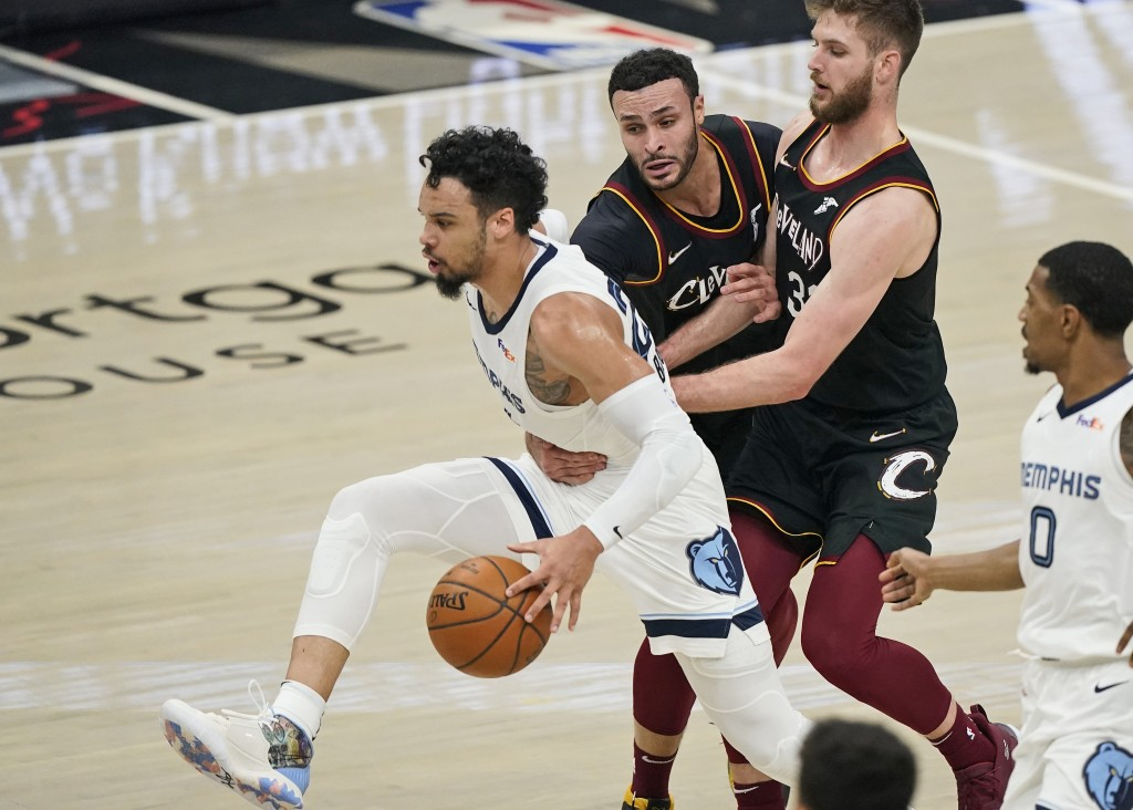 Memphis Grizzlies' Dillon Brooks, left, is fouled by Cleveland Cavaliers' Larry Nance Jr., second from left, in the first half of an NBA basketball ga...