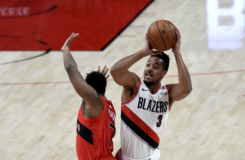 Portland Trail Blazers guard CJ McCollum, right, shoots over Toronto Raptors guard Kyle Lowry, left, during the first half of an NBA basketball game i...