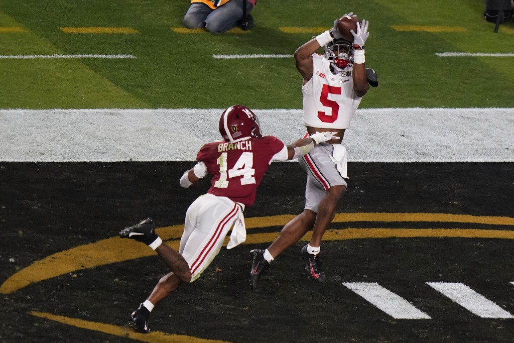 Ohio State wide receiver Garrett Wilson catches a touchdown pass in front of Alabama defensive back Brian Branch during the second half of an NCAA Col...