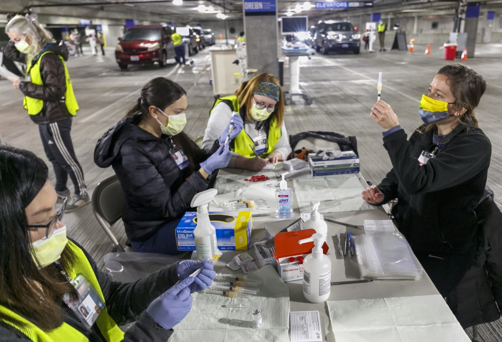FILE - In this Sunday, Jan. 10, 2021, file photo, Medical professionals from Oregon Health & Science University load syringes with the Moderna COVID-1...