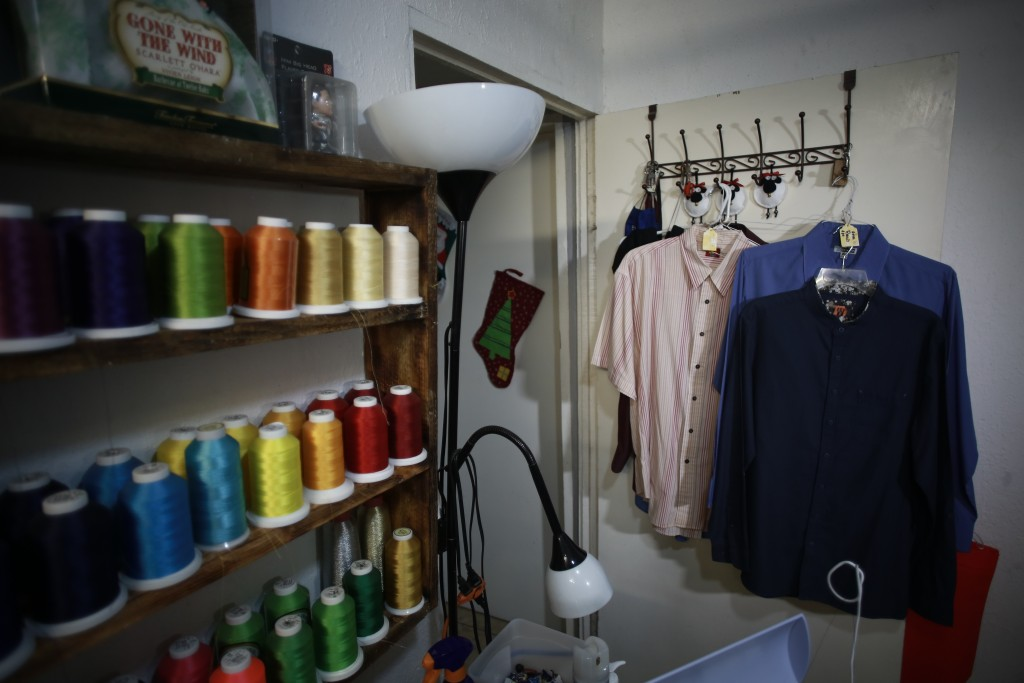 Shirts of people who died from COVID-19 hang in the home workshop of Erendira Guerrero, who uses the clothing to make stuffed bears for family members...