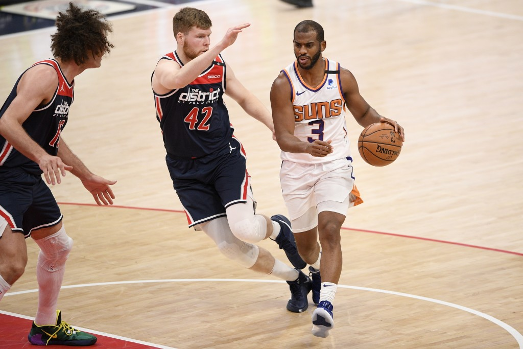 Phoenix Suns guard Chris Paul (3) dribbles next to Washington Wizards forward Davis Bertans (42) and center Robin Lopez (15) during the first half of ...