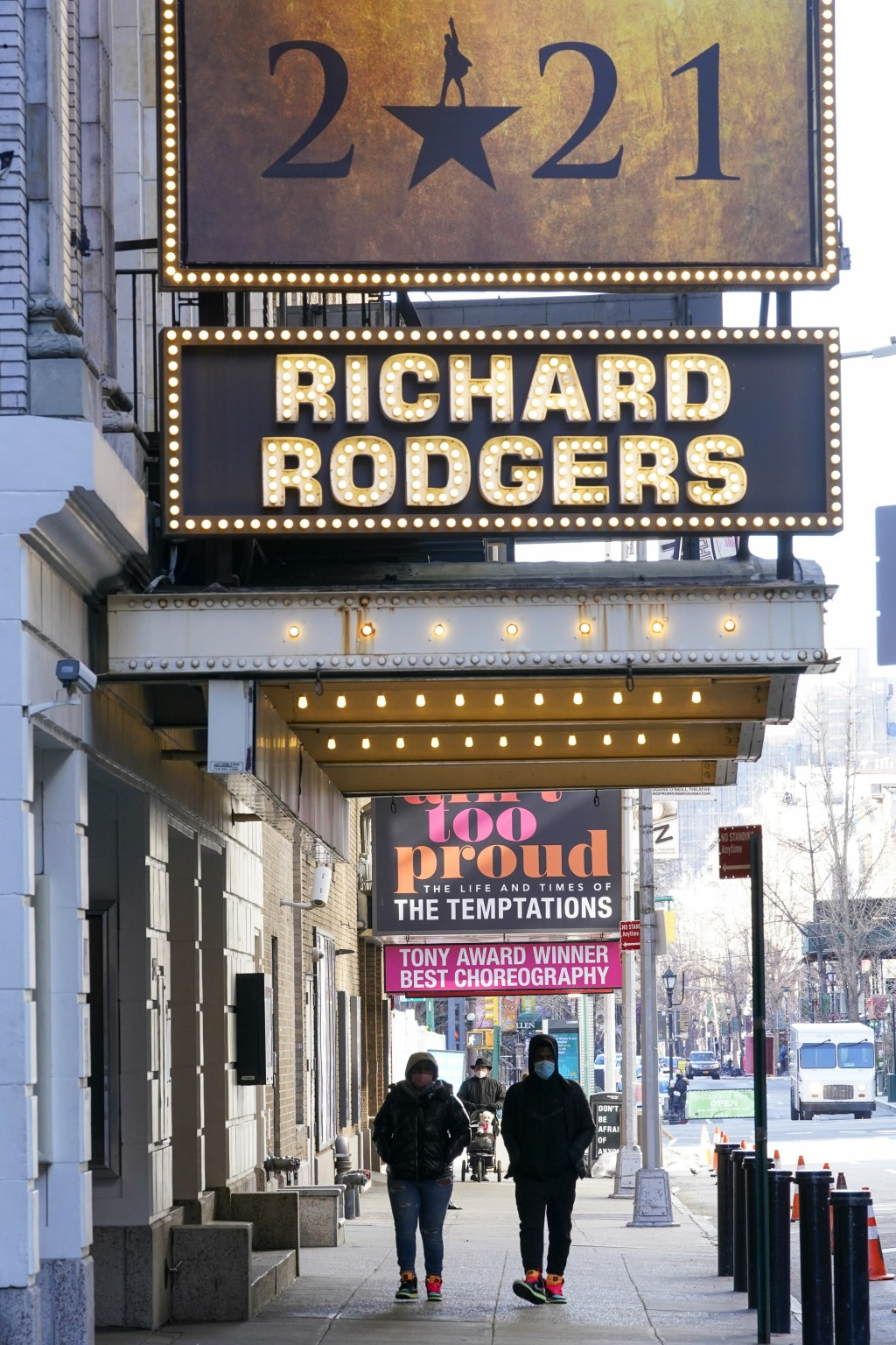Pedestrians walk past closed Theatres, Sunday, Jan. 10, 2021, in the Hell's Kitchen neighborhood of New York. The boarded-up windows and For Rent sign...