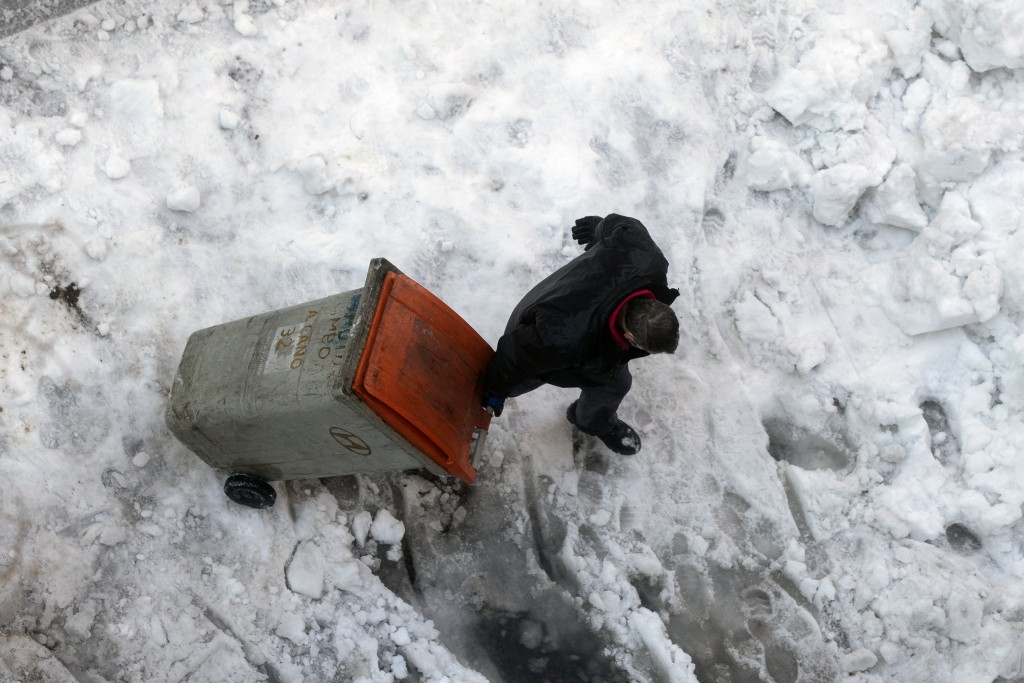 A man drags a garbage container through snow and ice in Madrid, Spain, Monday, Jan. 11, 2021. The Spanish capital is trying to get back on its feet af...