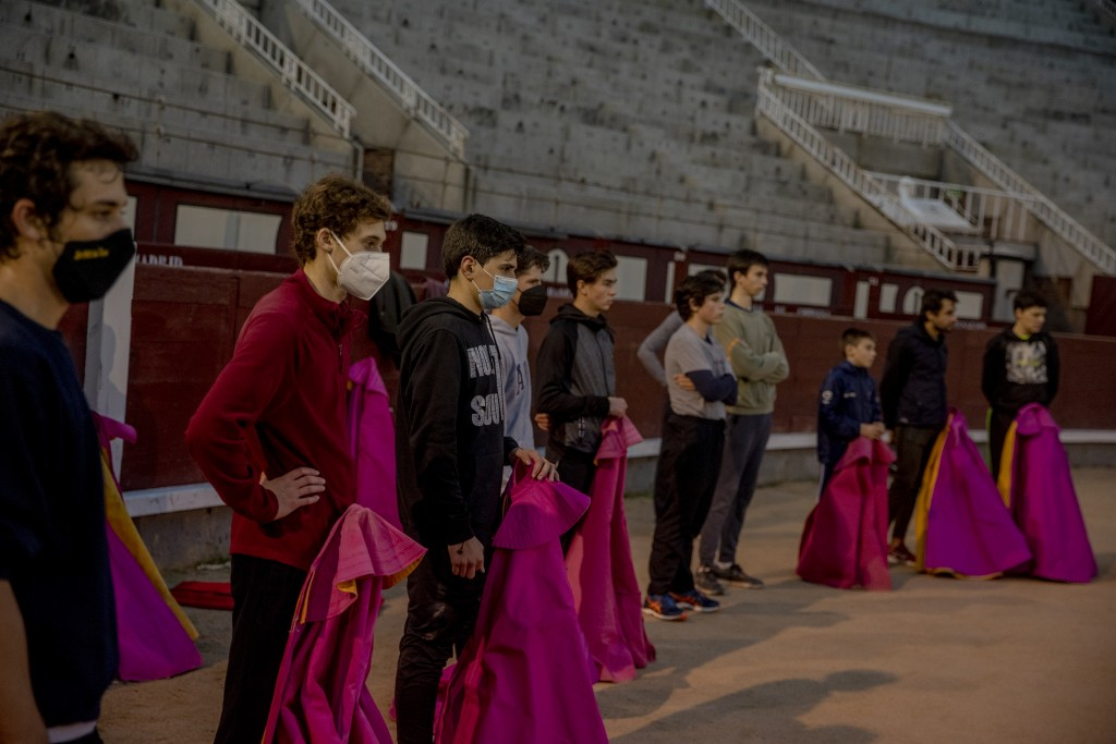 Pupils stand with their capes as they are instructed at the Bullfighting School at Las Ventas bullring in Madrid, Spain, Tuesday, Dec. 22, 2020. The s...