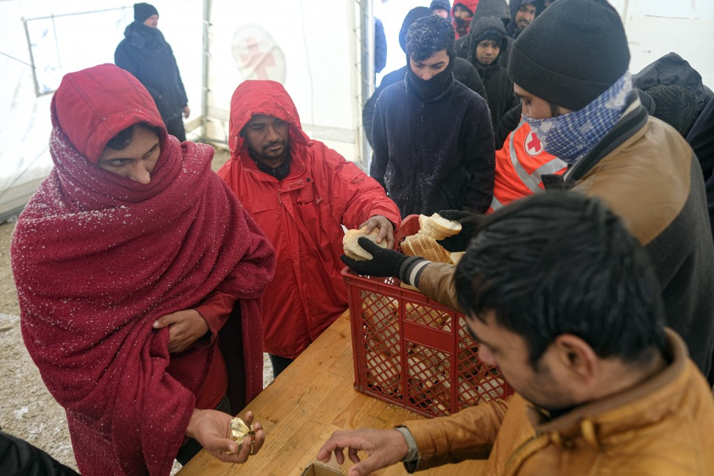 Migrants wait in a line to get food and warm beverages, at the Lipa camp, outside Bihac, Bosnia, Monday, Jan. 11, 2021. Aid workers say migrants stayi...