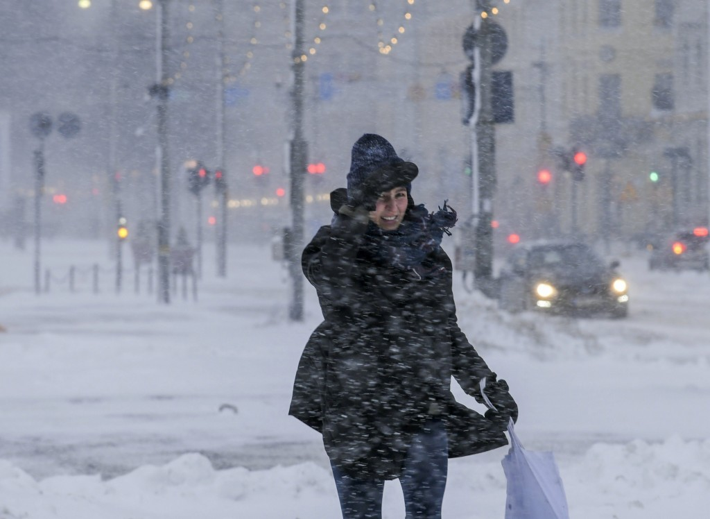 A woman struggles to walk along a street with thick layer of snow in Helsinki, Finland, making all kinds of travel difficult on Tuesday Jan. 12, 2021....