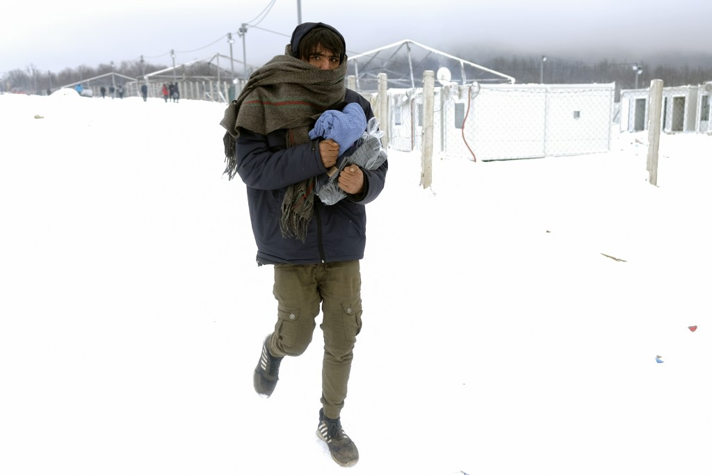 A migrant carries footwear and blankets received from humanitarian organization at the Lipa camp, outside Bihac, Bosnia, Monday, Jan. 11, 2021. Aid wo...
