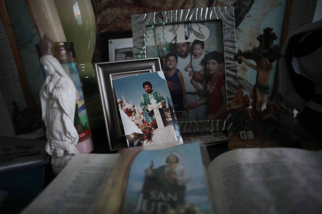 Pictures of Jaime Aguilar Rojas, who was 50 when he died of COVID-19 in November, adorn an altar in the home of his son, Jaime Walfre Aguilar Martinez...