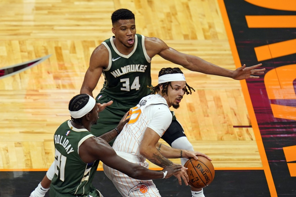 Orlando Magic guard Cole Anthony, center, looks to pass the ball as he is caught between Milwaukee Bucks guard Jrue Holiday, left, and forward Giannis...