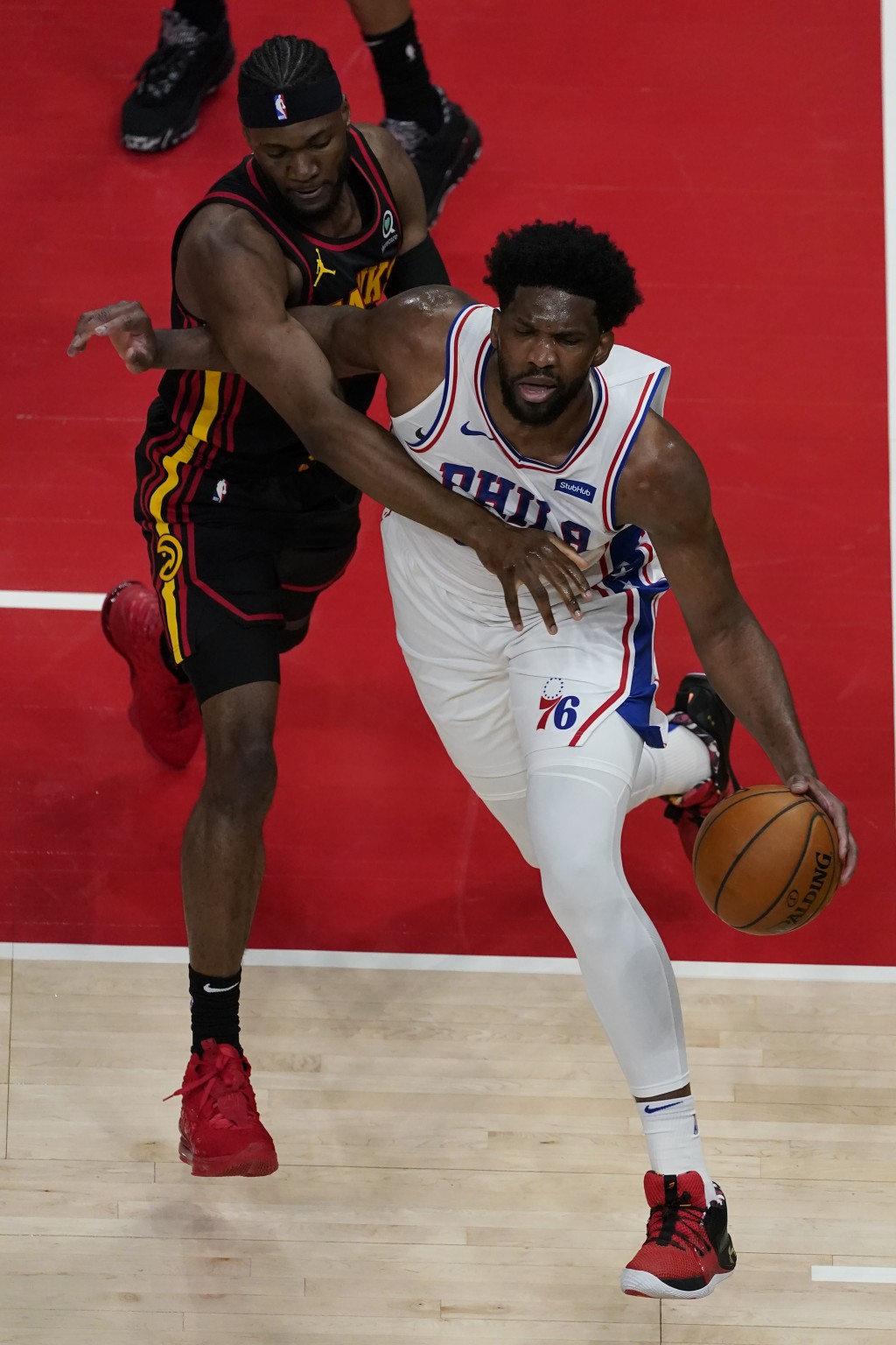 Philadelphia 76ers center Joel Embiid (21) drives past Atlanta Hawks forward Bruno Fernando (24) during the first half of an NBA basketball game Monda...