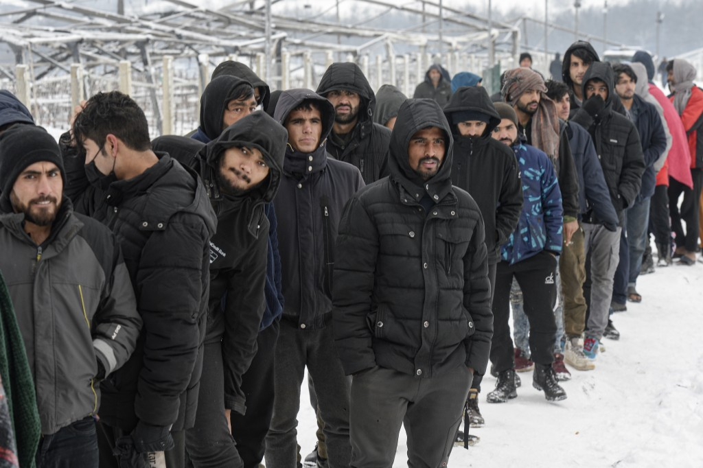 Migrants wait in a line to receive handouts of food and warm beverages, at the Lipa camp, outside Bihac, Bosnia, Monday, Jan. 11, 2021. Aid workers sa...