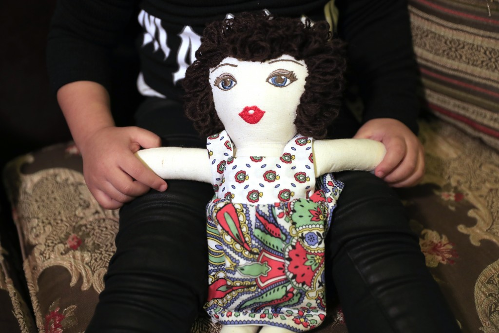 Sima-Rita, whose family home had the windows blown out during August's massive explosion in Beirut, holds her doll at her grandfather's home, in Beiru...