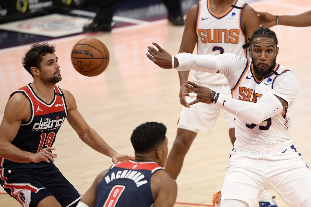 Phoenix Suns forward Jae Crowder, right, passes the ball against Washington Wizards guard Raul Neto (19) and forward Rui Hachimura (8) during the firs...