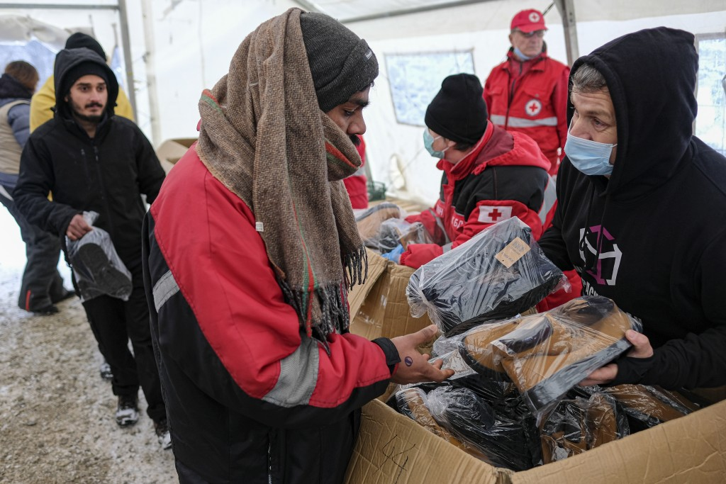 Migrants receive footwear and blankets from a humanitarian organization at the Lipa camp, outside Bihac, Bosnia, Monday, Jan. 11, 2021. Aid workers sa...