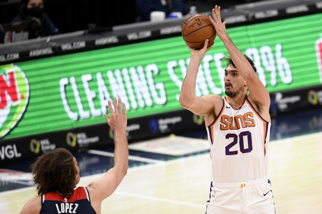 Phoenix Suns forward Dario Saric (20) shoots against Washington Wizards center Robin Lopez, left, during the first half of an NBA basketball game, Mon...