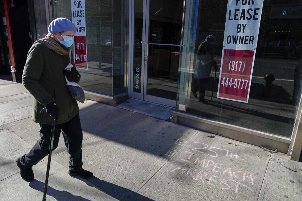 A pedestrian walks past a vacant commercial property and graffiti calling on President Trump to be removed from office and arrested, Sunday, Jan. 10, ...