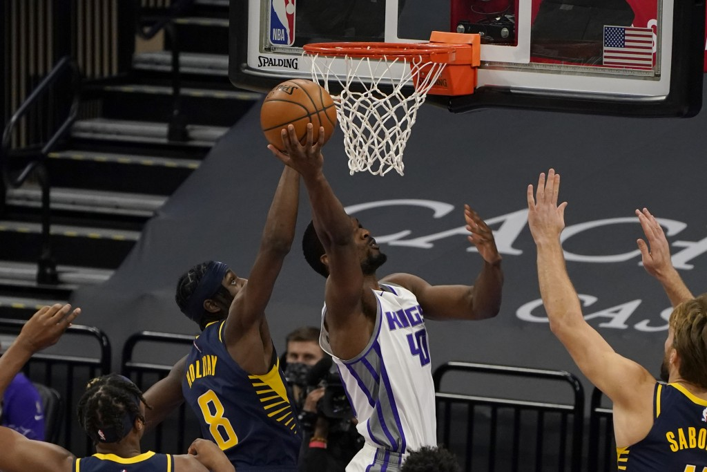 Sacramento Kings forward Harrison Barnes, right, goes to the basket past Indiana Pacers guard Justin Holiday during the first half of an NBA basketbal...