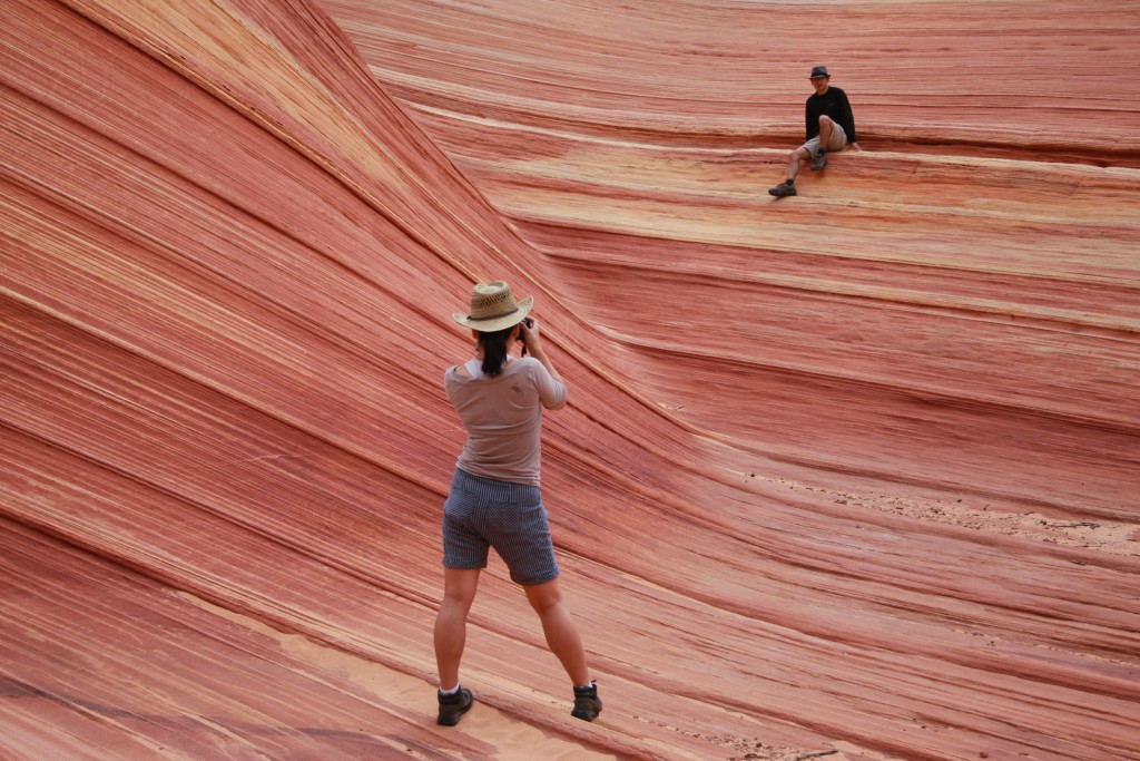 FILE - In this May 28, 2013, file photo, a hiker takes a photo on a rock formation known as The Wave in the Vermilion Cliffs National Monument in Ariz...