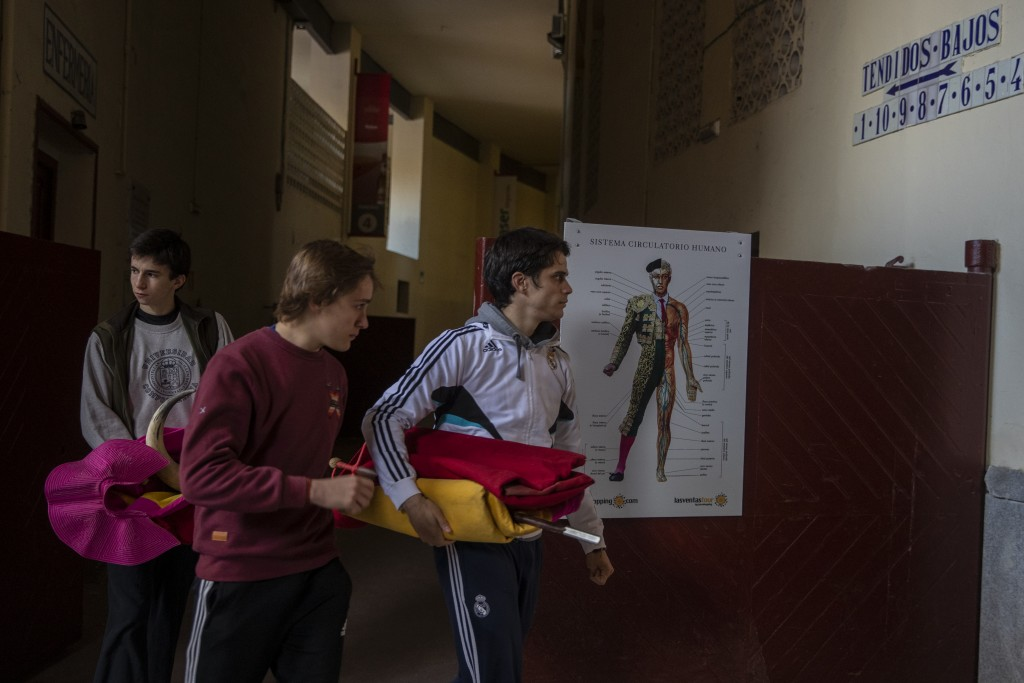 Pupils holding red capes and a sword arrive at the Bullfighting School at Las Ventas bullring in Madrid, Spain, Tuesday, Dec. 29, 2020. The school was...