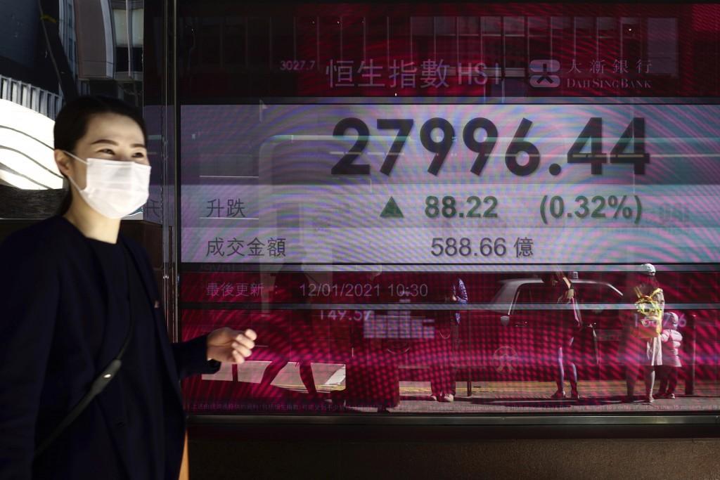 A woman walks past a bank's electronic board showing the Hong Kong share index at Hong Kong Stock Exchange in Hong Kong Tuesday, Jan. 12, 2021. Asian ...