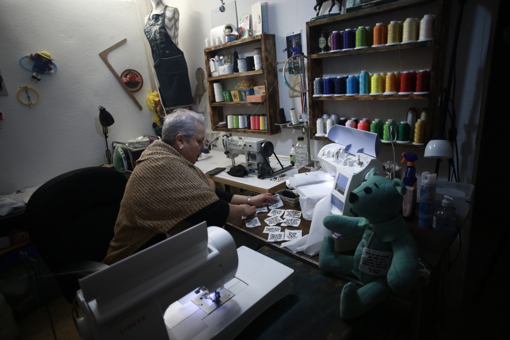 Erendira Guerrero makes stuffed bears for people who lost a family member to COVID-19, using one of the deceased's articles of clothing, at her home w...