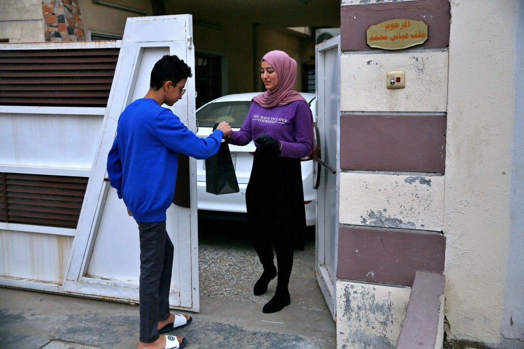 Fatima Ali hands her takeaway cheese-plate to a customer in Baghdad, Iraq, Saturday, Nov. 28, 2020. After Iraq imposed a coronavirus lockdown in March...
