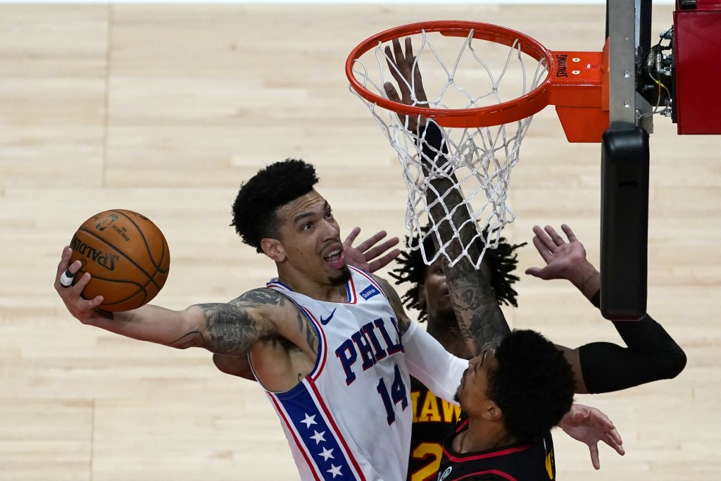 Philadelphia 76ers forward Danny Green (14) goes in for a basket as Atlanta Hawks' John Collins (20), right, and Bruno Fernando (24) defends during th...