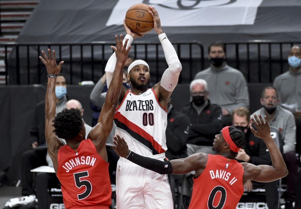 Portland Trail Blazers forward Carmelo Anthony, center, shoots over Toronto Raptors forward Stanley Johnson, left, and guard Terence Davis, right, dur...