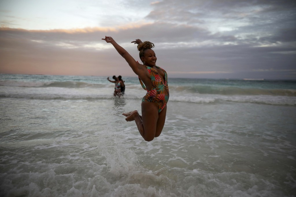An American tourist poses for a photo while jumping in the air photo in the shallow waters of a beach in Tulum, Quintana Roo state, Mexico, Monday, Ja...