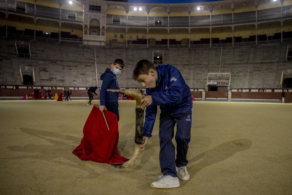 Pupils Nicolas Sanz Luna, 10, right, performs holding a plastic bull horns with Daniel at the Bullfighting School at Las Ventas bullring in Madrid, Sp...