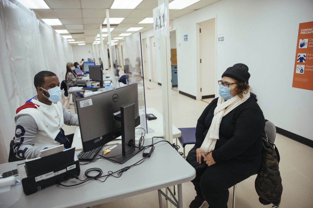 FILE - In this Sunday, Jan. 10, 2021, file photo, Teresa Jimenez sits with a navigator during the registration process at the COVID-19 vaccination fac...