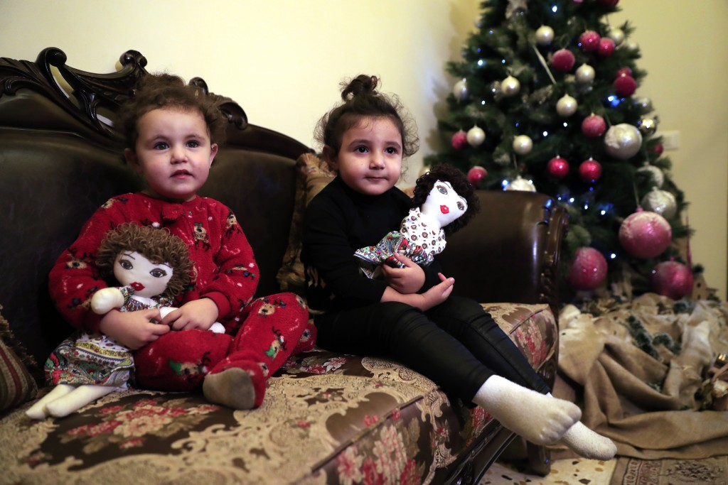 Sama Chlawuit, left, and her sister Sima-Rita, whose family home had the windows blown out during August's massive explosion in Beirut, hold their dol...