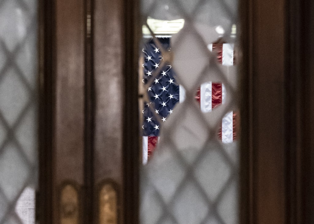 Broken glass from last week's confrontation with a pro-Trump mob is seen in the door to the House chamber at the Capitol in Washington, Tuesday, Jan. ...
