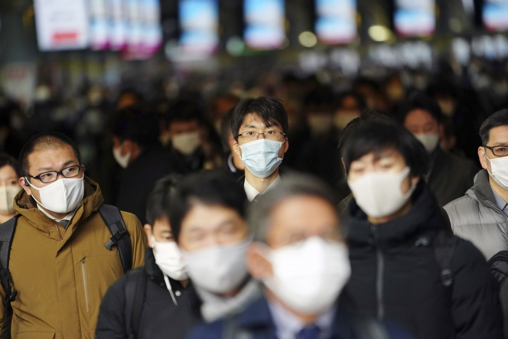 FILE - In this Jan. 4, 2021, file photo, people commute on the first business day of the year at a train station in Tokyo. Opposition to the Tokyo Oly...