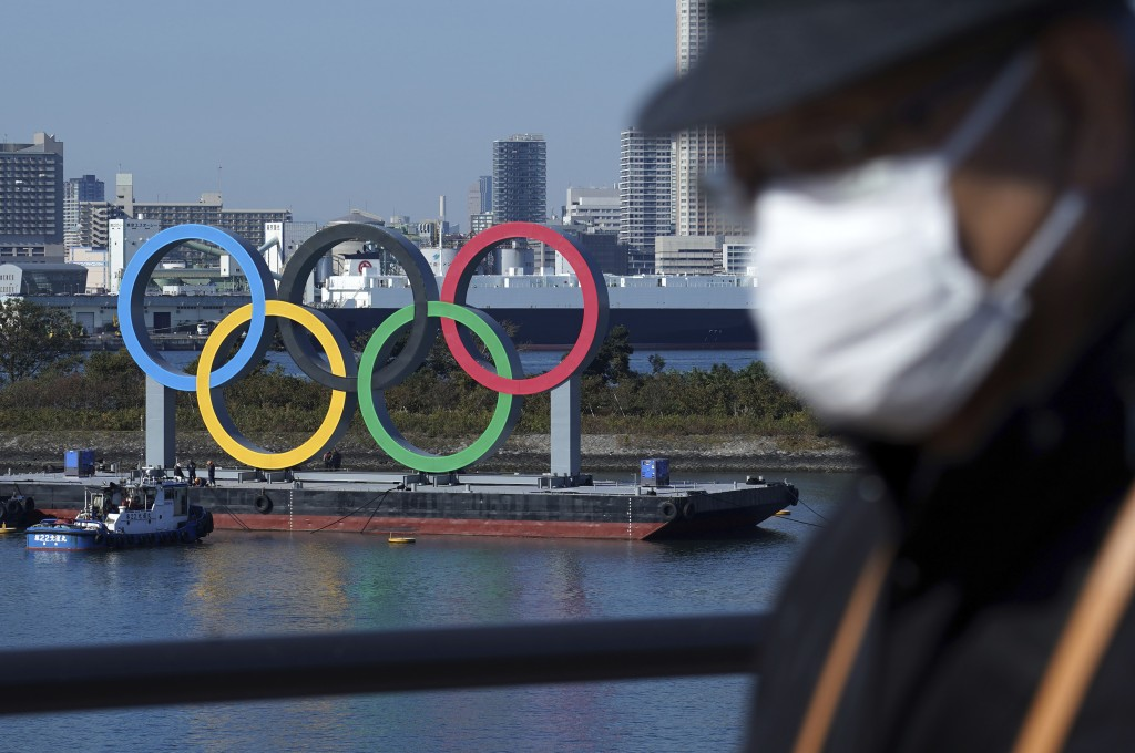 FILE - In this Dec. 1, 2020, file photo, a man wearing a protective face mask to help curb the spread of the coronavirus walks with the Olympic rings ...