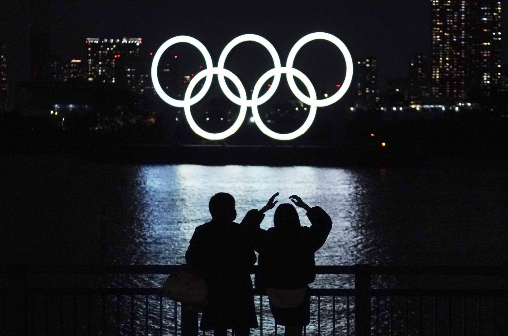 FILE - In this Dec. 1, 2020, file photo, a man and a woman look at the Olympic rings float in the water in the Odaiba section in Tokyo. Opposition to ...