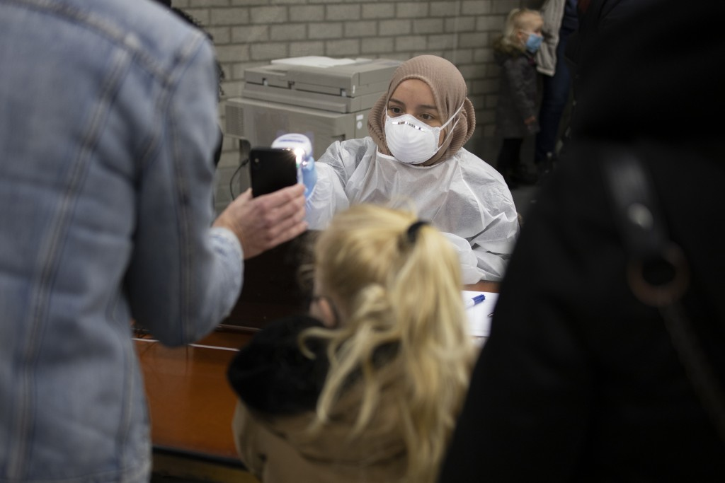 Residents of Bergschenhoek, Netherlands, register as they take part in a mass test of all of the municipality's 62,000 residents starting Wednesday, J...