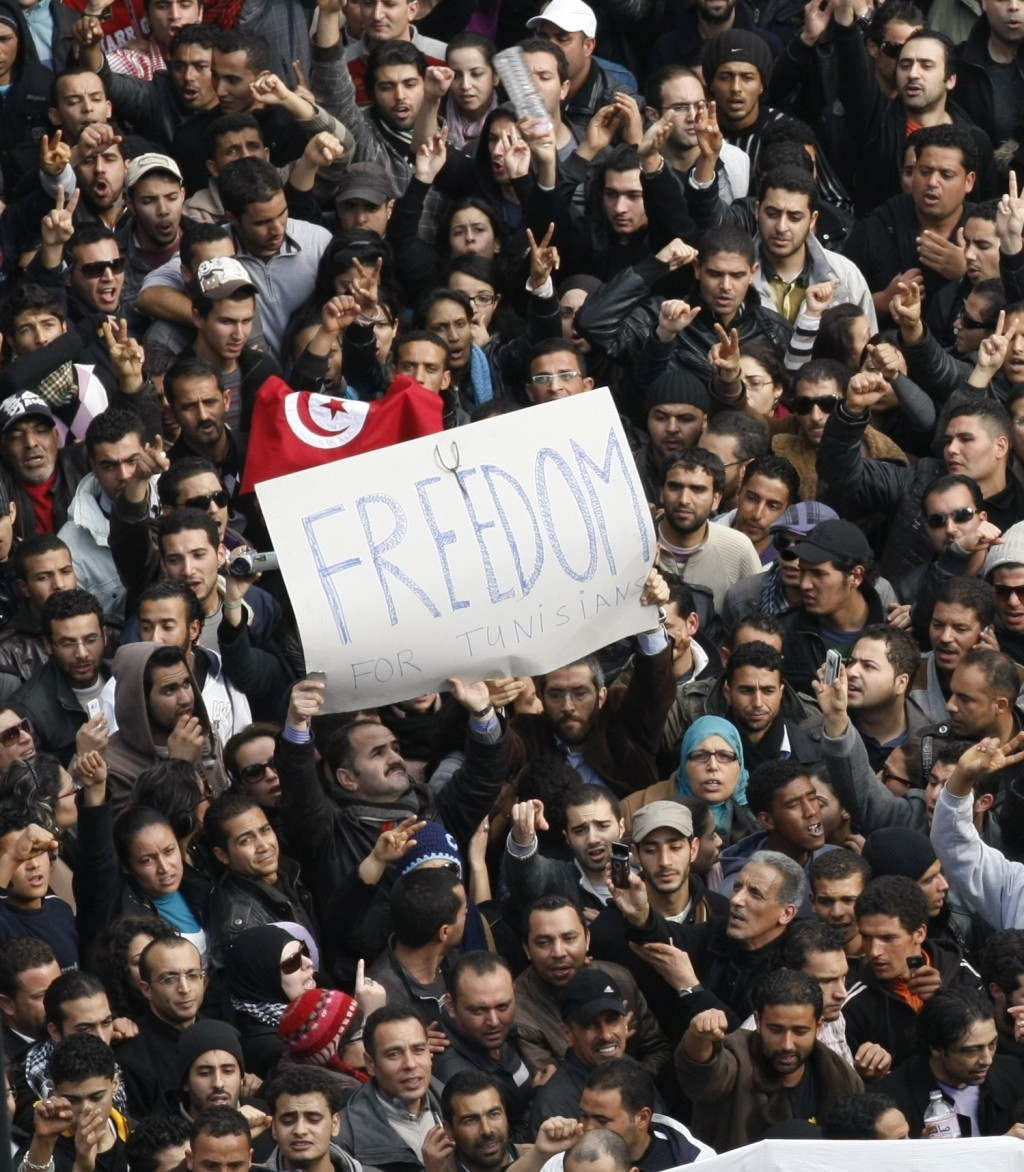 FILE - In this Jan. 14, 2012 file photo, protesters chant slogans against President Zine El Abidine Ben Ali in Tunis. Since winning a parliamentary se...