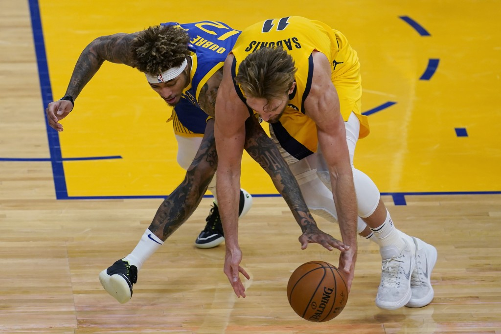 Golden State Warriors guard Kelly Oubre Jr., left, reaches for the ball next to Indiana Pacers forward Domantas Sabonis during the first half of an NB...