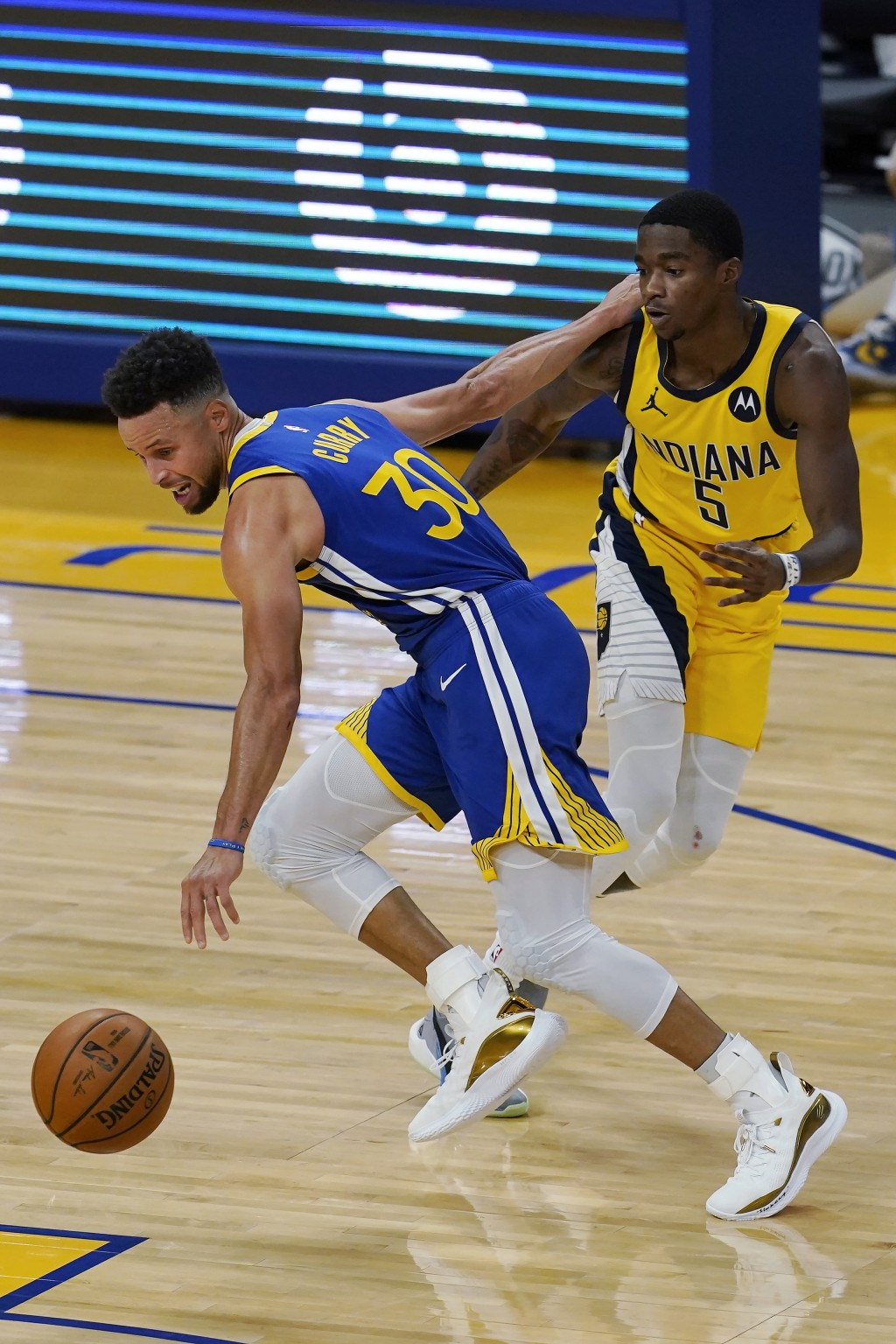 Golden State Warriors guard Stephen Curry (30) drives against Indiana Pacers guard Edmond Sumner (5) during the first half of an NBA basketball game i...
