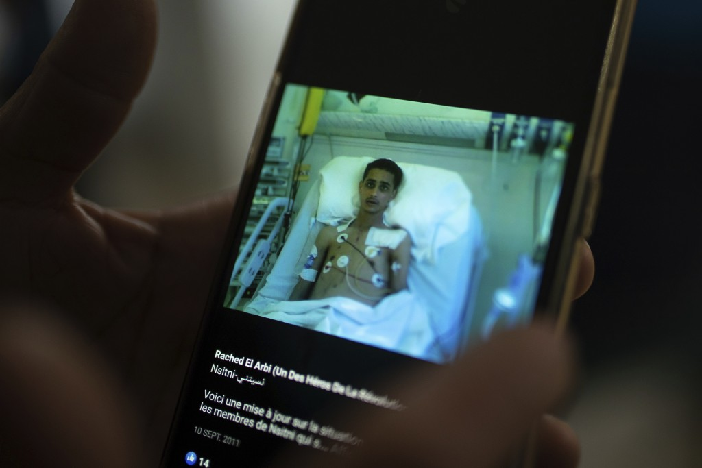 The mother of Rached El Arbi, a protester who was paralyzed after being shot during Tunisia's democratic uprising 10 years ago, holds a photo of her s...