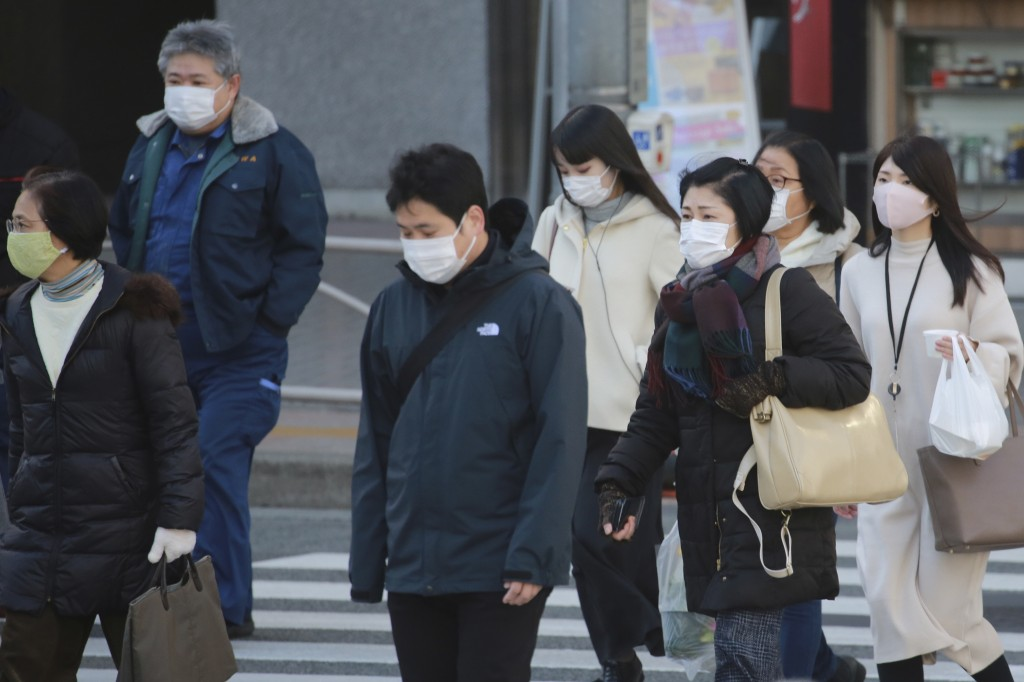 People wearing face masks to protect against the spread of the coronavirus cross an intersection on a street in Tokyo, Wednesday, Jan. 13, 2021. (AP P...