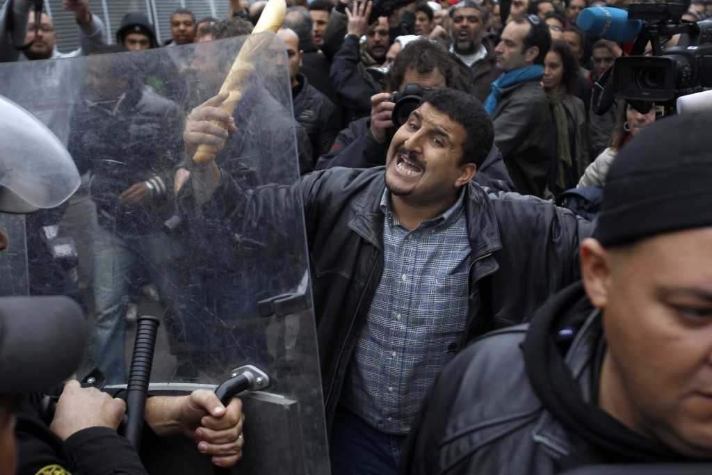 FILE - In this Jan. 18, 2011 file photo, a protestor faces riot police officers during a demonstration against the party of Tunisian ruler Ben Ali, in...