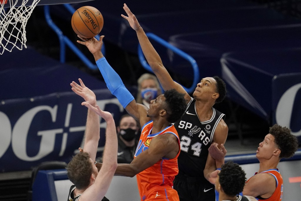 Oklahoma City Thunder guard Hamidou Diallo, center, goes to the basket between San Antonio Spurs center Jakob Poeltl, left, and guard Devin Vassell (2...