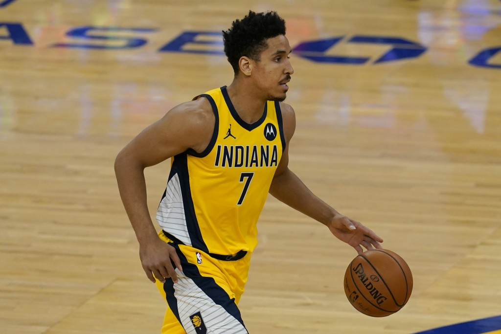 Indiana Pacers guard Malcolm Brogdon (7) dribbles the ball up the court against the Golden State Warriors during the first half of an NBA basketball g...