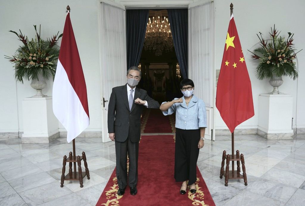 In this photo released by Indonesian Foreign Ministry, Chinese Foreign Minister Wang Yi, left, poses for photographers with his Indonesian counterpart...