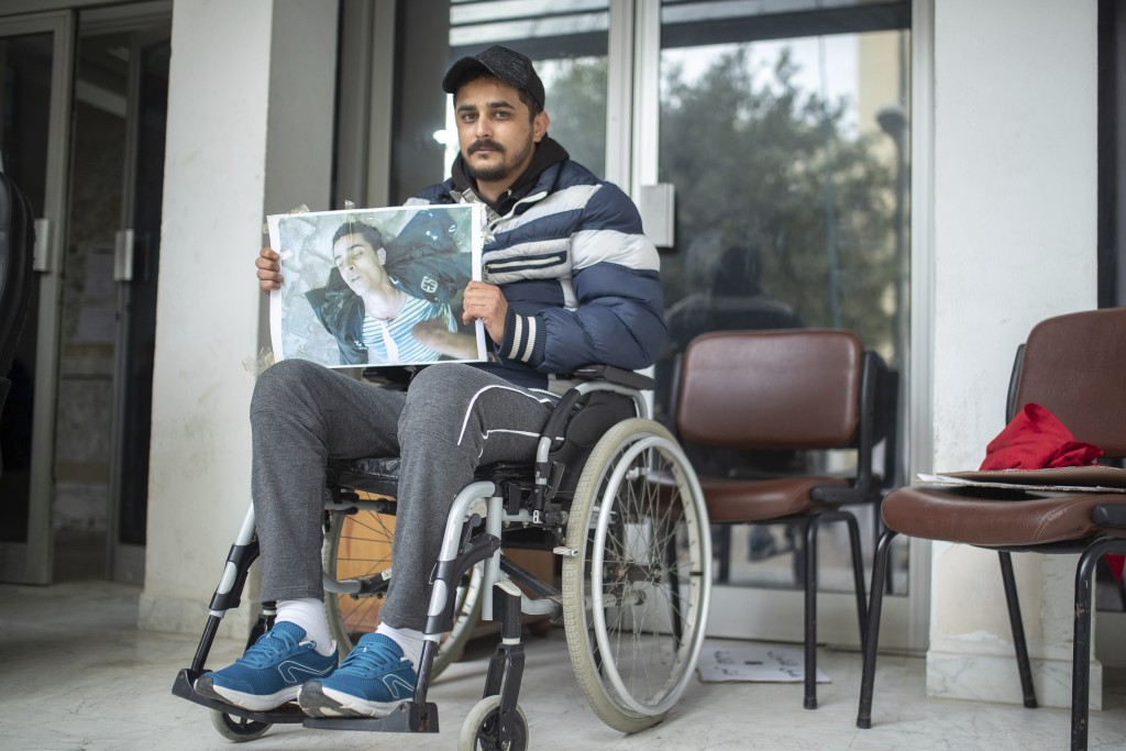 Rached El Arbi, 30, a protester who was paralyzed after being shot during Tunisia's democratic uprising 10 years ago, poses for a portrait while holdi...