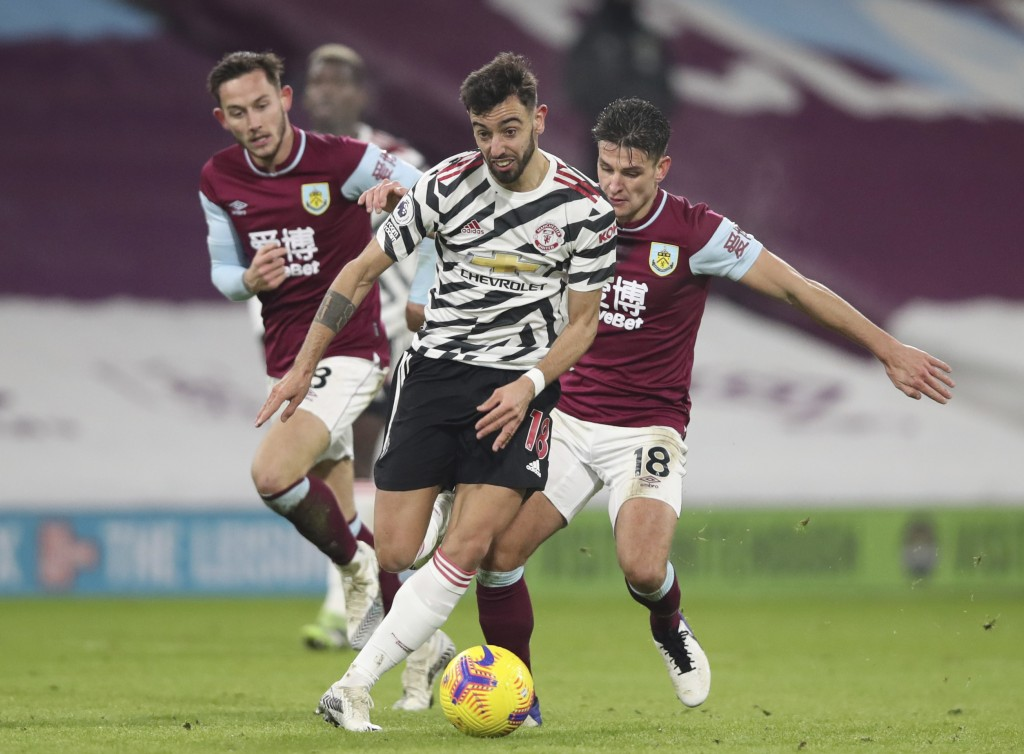 Manchester United's Bruno Fernandes, center, runs with the ball after dribbling past Burnley's Ashley Westwood, right, during the English Premier Leag...