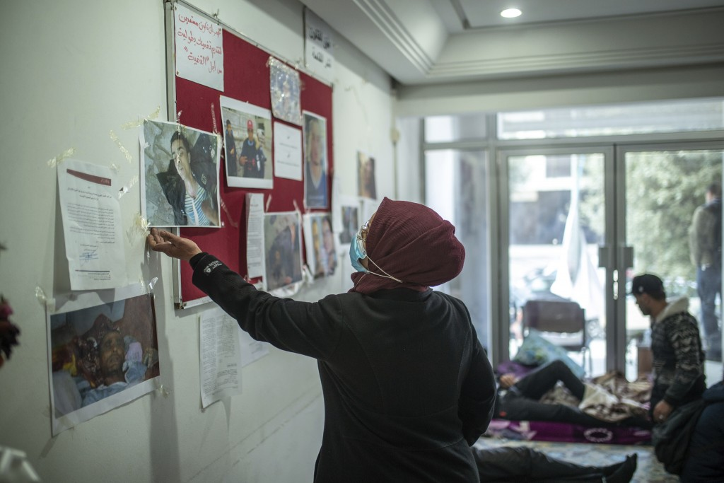 The mother of Rached El Arbi, a protester who was paralyzed after being shot during Tunisia's democratic uprising 10 years ago, holds a portrait of he...